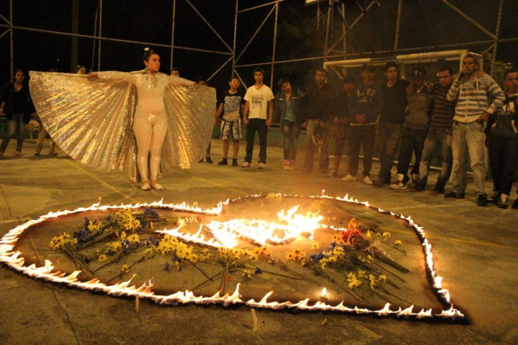 A person dressed in white clothes and cape stands arms spread, as if spreading their wings while a group of other people stands behind them. On the ground, fire has been lit in a shape of a heart and it has been filled with flowers and burning letters.
