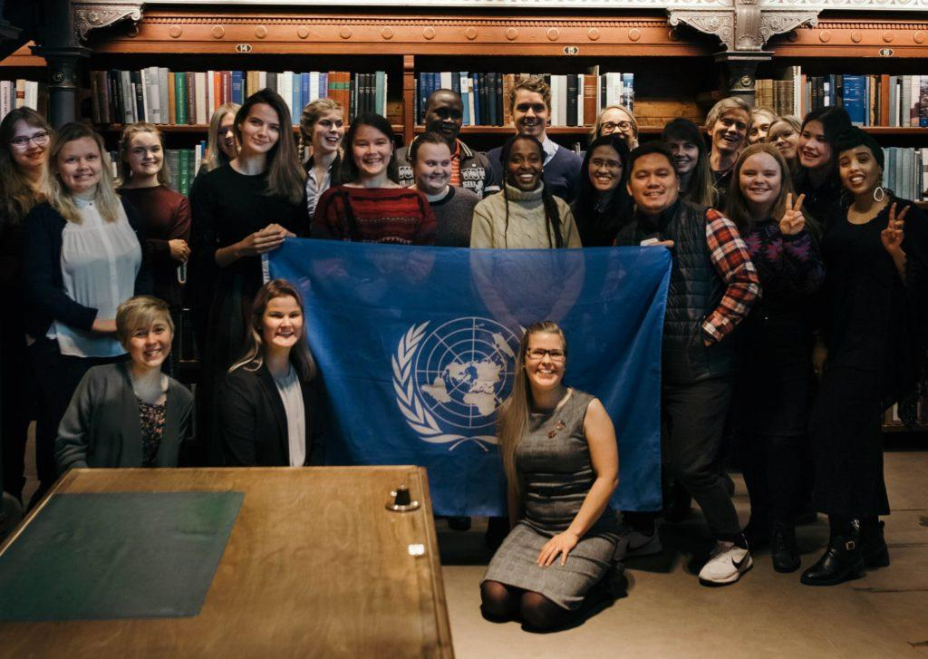 A group of young people stands and sits in front of a bookshelf. They hold the flag of the United Nations.