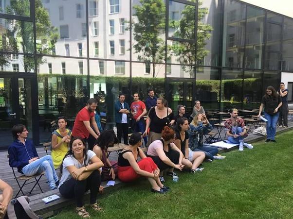 Joukko ihmisiä istuu maassa ja tuoleilla ja seisoo lasiseinäisen rakennuksen edustalla.