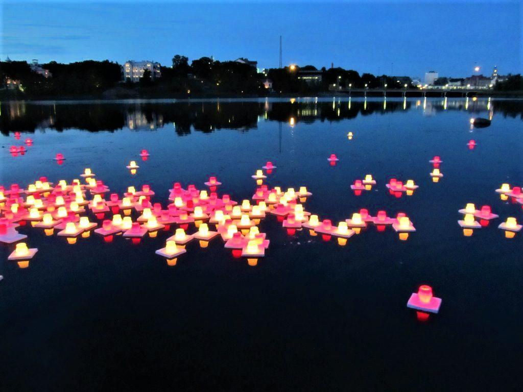 Atomipommien uhrien muistoksi sytytettyjä kynttilälyhtyjä kellumassa järvellä