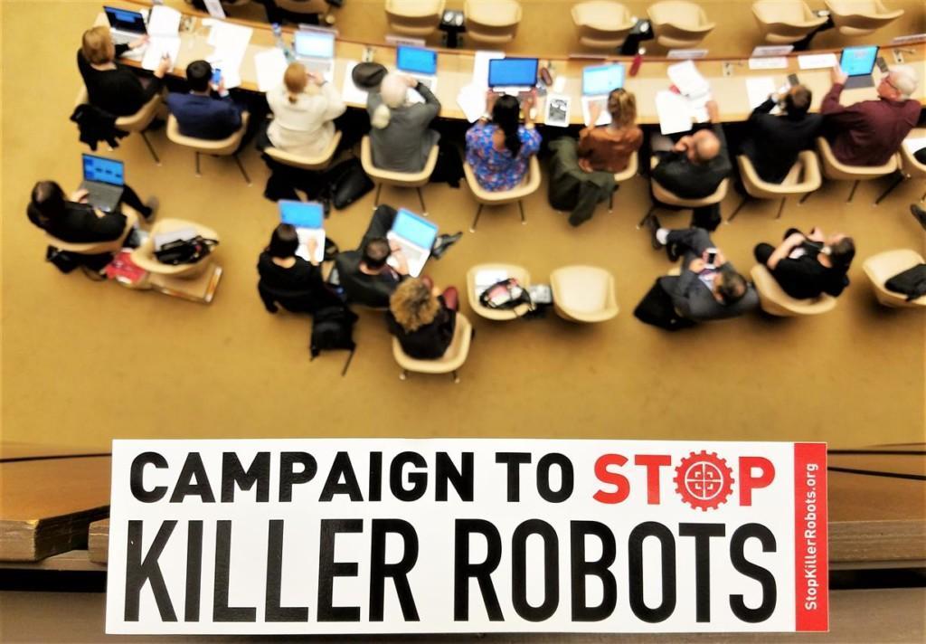 Campaign to Stop Killer Robots tarra ja taustalla ihmisiä istuntosalissa